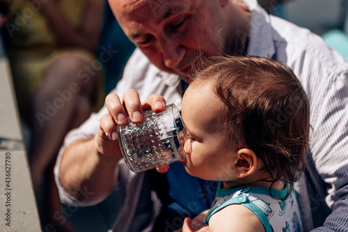 Canvastavla caring father giving water to his baby on a hot summer day