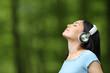 Leinwandbild Motiv Asian woman breathing listening music with headphones
