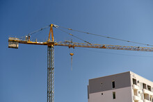 Construction Crane Over A Finished Block Of Flats Against A Blue Sky Background. Close Up