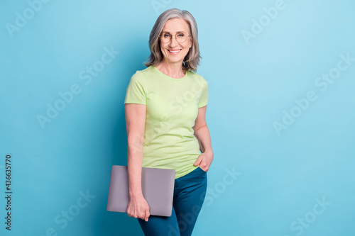 Photo of attractive charming old woman hold hands laptop wear glasses smile isolated on blue color background