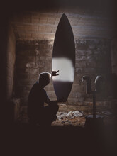 Man Inspecting Surf Board In Darkness