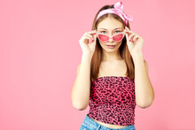 Cool Hipster Girl Wearing Stylish Glasses. Positive Young Woman Looking At Camera On Pink Background. Caucasian Female University Student Posing.