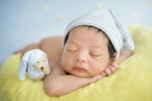 Close Up Newborn Baby Wearing A Blue And White Striped Hat. Newborn Sleeping On A Crescent Moon Pillow On Sky Blue Background. A Teddy Bear Beside Newborn Also Wear The Same Hat.