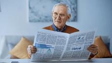 Elderly Man In Glasses Reading Newspaper At Modern Living Room.