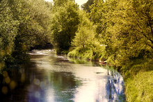 The Small River Aller Near Gifhorn In Germany In Bright Sunlight With A Canoe For A Boat Trip, Backlight With Sun Flare