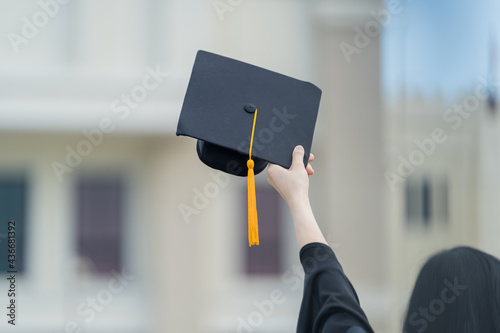 Papel de parede A young beautiful Asian woman university graduate in graduation gown and mortarb