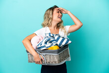 Young Brazilian Woman Holding A Clothes Basket Isolated On Blue Background Smiling A Lot