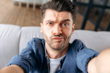 Portrait Of A Young Adult Puzzled Caucasian Man In Casual Clothes Sitting On The Couch, Taking A Selfie, Grimacing While Shooting, Uses A Smartphone, Fooling Around, Looking At The Frontal Webcam