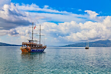 Vintage Mast Wooden Sailing Ship For Sea Tours In Saranda Gulf, Albania With Red State Albanian Flag With Black Double-headed Eagle. Small Yacht And Corfu Island On The Horizon
