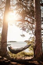 Man Sleeping In Hammock At Lakeshore