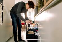 Full Length Of Teenage Boy Throwing Garbage In Bin At Home
