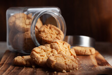 Close-up Of Delicious Freshly Baked Simple Cookies Or Biscuits Coming Out From A Glass Jar . Over A Wooden Top  Background.