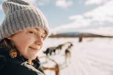 Portrait Of Teenage Girl Wearing Knit Hat Doing Dogsledding During Winter