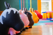 Close Up, Selective Focus Shot Of A Row Of Colored Plastic Toy Horses Neatly Arranged In The Toys And Game Area In A Canadian Kindergarten.
