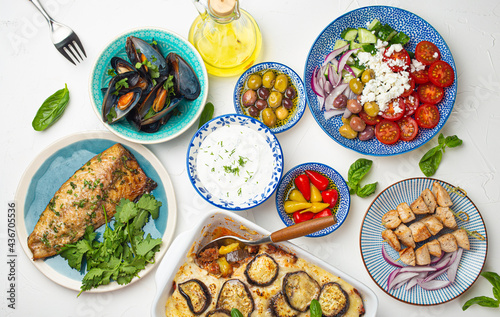 Canvas Assorted Greek dishes on white stone background from above, moussaka, grilled fi