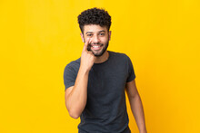Young Moroccan Man Isolated On Yellow Background Showing Something