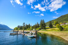 Beautiful Sunny Day In Lake Alice. The View On The Quiet Harbour With A Few Sailing Boats. Green Mountains, Trees And Blue Sky With White Clouds In The Background.