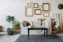 Bohemian Room With Couch And Empty Frames Above