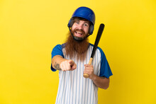 Redhead Baseball Player Man With Helmet And Bat Isolated On Yellow Background Surprised And Pointing Front
