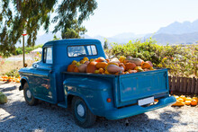 A Vintage Blue Pickup Truck Loaded With Colorful Pumpkins.