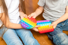 Anti Stress Sensory Pop It Toy In A Children's Hands. A Little Happy Kids Sharing And Plays With A Simple Dimple Toys At Home. Toddlers Holding And Playing Rainbow Popit, Trend 2021 Year