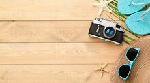 Sun Hat, Flip Flops, Camera, Sunglasses Palm Leaf And Starfish On Wooden Background