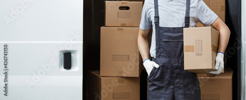 Fotografie, Obraz A young handsome smiling worker wearing uniform is standing next to the van full of boxes holding a box in his hands