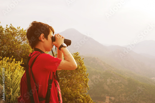 Carta da parati Boy watches the birds through the binoculars against the background of the mountains