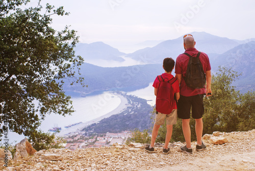 Carta da parati Father and son watch from the top, from the observation deck of the mountains to the sea, mountains, city and beach in Oludeniz, Turkey on a summer evening