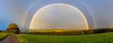Beautiful full rainbow on the blue sky above the green field and trees