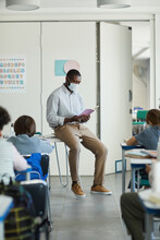 Full Length Portrait Of African-American Male Teacher Wearing Mask In School Classroom, Covid Safety Measures
