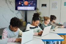 Diverse Group Of Children Sitting In Row At School Classroom And Using Computers