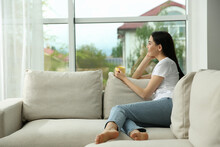 Young Woman With Cup Of Coffee Relaxing On Sofa At Home, Space For Text