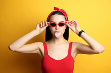Fashionable Young Woman In Pin Up Outfit Blowing Bubblegum On Yellow Background