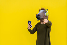 Woman With Horse Head Mask And Headphones Using Smartphone ,pointing Finger At Camera Isolated Over Yellow Background In Studio