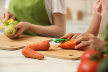 Mother And Daughter Peeling Vegetables At Table In Kitchen, Closeup