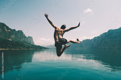 Fotografie, Obraz Man jumping with joy by a lake