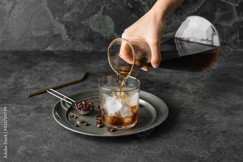 Pouring of cold brew coffee from jug into glass on grunge background