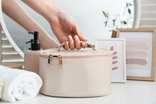Female Hand With Stylish Cosmetic Bag On Table In Room