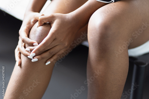 Fotografiet Black African young woman having knee joint pain or knee injury problem, concept