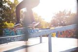 Skater is doing ollie on the ramp in a skatepark in sunny day
