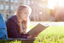 Young Woman Student Is Reading Book, Lying On Green Grass Yard Near College Building. Smart Blond Girl Is Studying, Preparing To Exam At University Campus. Education Concept. High School Lifestyle.