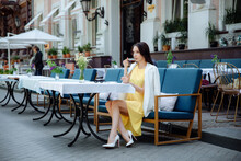 Stylish Young Woman Or Teenage Girl With Cup Drinking Coffee At City Street Cafe Terrace. Girl In A Yellow Dress And White Jacket
