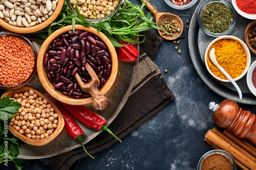 Photo Legumes, lentils, chickpea, beans assortment, tasty appetizing ingredients spices grocery for cooking healthy kitchen on black table