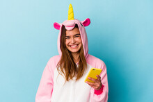 Young Caucasian Woman Wearing A Unicorn Pajama Holding A Mobile Phone Isolated On Blue Background