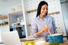 Happy Woman In Kitchen Following Recipe On Digital Device During Cooking.
