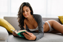 Erotic, Sensuality Woman Concept. Portrait Of Sexy Woman Reading Book In Lingerie.