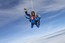 Skydiving. Tandem Jump. A Young Woman And Her Instructor Are In The Sky.