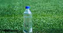 Water Bottle On Green Grass For Hydration, Thirst