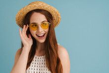 Young Ginger Woman In Sunglasses Smiling And Looking Aside